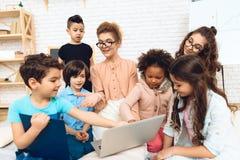 O grupo de crianças junto com o professor está estudando como trabalhar com portátil fotos de stock