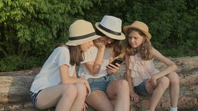 O grupo de crianças, três meninas que sentam-se sobre entra a natureza e a vista do smartphone filme