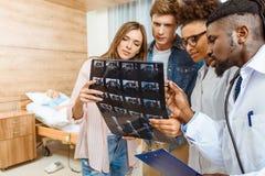 O grupo de doutores e os pacientes que examinam o raio X fotografam na foto de stock royalty free