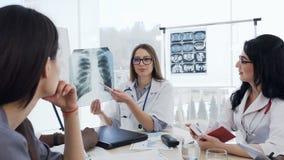 O grupo de doutores qualificados está analisando o raio X dos pulmões um paciente Sa?de e conceito m?dico filme