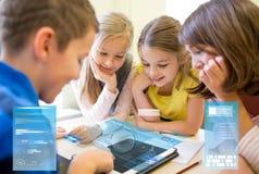 O grupo de escola caçoa com o PC da tabuleta na sala de aula fotografia de stock royalty free