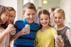 O grupo de escola caçoa com smartphone e latas de soda Foto de Stock