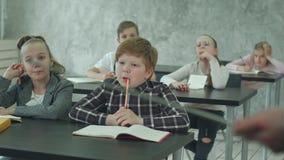 O grupo de escola caçoa na classe junto, escutando o professor video estoque