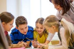 O grupo de escola caçoa o teste da escrita na sala de aula