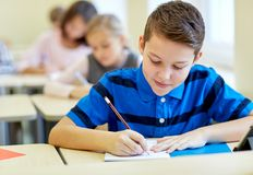 O grupo de escola caçoa o teste da escrita na sala de aula Fotos de Stock Royalty Free