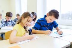 O grupo de escola caçoa o teste da escrita na sala de aula Fotografia de Stock