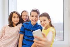 O grupo de escola caçoa a tomada do selfie com smartphone Imagens de Stock Royalty Free