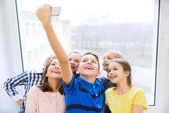 O grupo de escola caçoa a tomada do selfie com smartphone Foto de Stock
