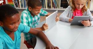 O grupo de escola caçoa usando a tabuleta e o portátil digitais na biblioteca filme