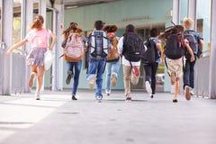 O grupo de escola primária caçoa o corredor na escola, vista traseira fotos de stock royalty free