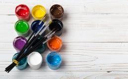 O grupo de escovas diferentes e de pinturas acrílicas a pintar dispersou em uma tabela de madeira escura Fundo do local de trabal fotografia de stock royalty free
