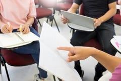 O grupo de estudantes adulto escuta a leitura do professor e pergunta pedir na sala de classe pequena no campus universitário imagem de stock
