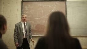 O grupo de estudantes em uma sala de aula, escutando como seu professor guarda uma leitura vídeos de arquivo