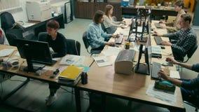 O grupo de estudantes está trabalhando em computadores na universidade na sala da educação da TI filme