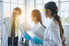 O grupo de estudantes de Medicina asiáticas pesquisa o projeto novo com o professor superior no laboratório fotos de stock royalty free
