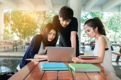 O grupo de estudantes novo consulta com os dobradores da escola, laptop foto de stock