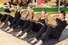 O grupo de execução atlética das mulheres adultas senta acima exercícios para reforçar seus músculos abdominais do núcleo no trei fotos de stock royalty free