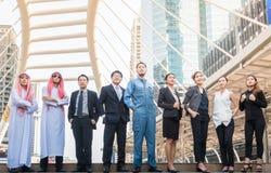 O grupo de executivos do international tem o árabe, o coordenador, o homem de negócios Meeting com por do sol e o fundo da cidade imagens de stock royalty free