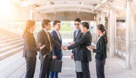 O grupo de executivos que agitam as mãos, trabalhos de equipa que terminam acima uma reunião partners o cumprimento de após ter a fotos de stock