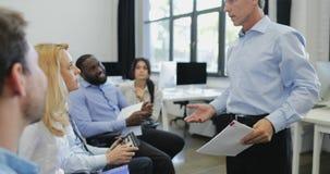 O grupo de executivos que escutam a apresentação faz a pergunta em reunião principal do treinamento do homem de negócios maduro d video estoque