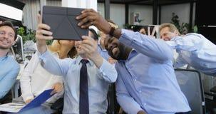 O grupo de executivos que tomam a foto do selfie no tablet pc no escritório moderno, equipe moderna faz o autorretrato filme