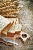 O grupo de faca da placa de desbastamento cortou as orelhas do centeio do pão na parte traseira de serapilheira Imagens de Stock Royalty Free