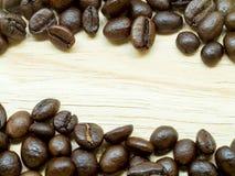 O grupo de feijões de café finos está no fundo de madeira claro Foto de Stock