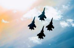 O grupo de fulgor do sol do avião do avião de combate de quatro aviões tonificou o céu imagem de stock royalty free