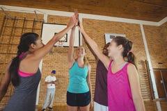 O grupo de High School caçoa a doação da elevação cinco no campo de básquete Imagem de Stock