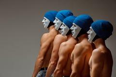 O grupo de homens caucasianos nas máscaras e nos chapéus brancos, calças de brim Imagem de Stock Royalty Free