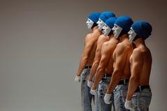 O grupo de homens caucasianos nas máscaras e nos chapéus brancos, calças de brim Foto de Stock