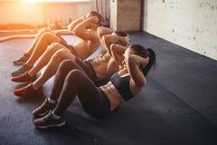 O grupo de homens e de mulheres que adultos atléticos executar se senta exercita acima imagem de stock royalty free