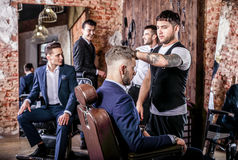 O grupo de homens positivos elegantes novos levanta no interior do barbeiro fotografia de stock royalty free