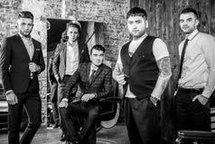 O grupo de homens positivos elegantes novos levanta no interior do barbeiro fotos de stock