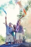 O grupo de indivíduos novos tem o divertimento com as fugas do fumo colorido Imagens de Stock