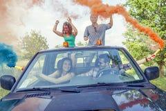 O grupo de indivíduos novos tem o divertimento com as fugas do fumo colorido Foto de Stock