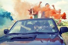 O grupo de indivíduos novos tem o divertimento com as fugas do fumo colorido Fotos de Stock