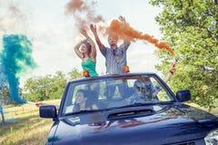 O grupo de indivíduos novos tem o divertimento com as fugas do fumo colorido Imagem de Stock