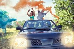 O grupo de indivíduos novos tem o divertimento com as fugas do fumo colorido Fotos de Stock Royalty Free