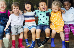 O grupo de jardim de infância caçoa amigos arma-se em torno do assento e do smilin imagem de stock