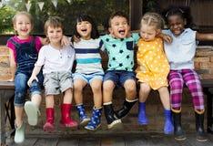 O grupo de jardim de infância caçoa amigos arma-se em torno do assento e do smilin imagens de stock royalty free