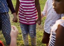 O grupo de jardim de infância caçoa os amigos que guardam as mãos que jogam no parque imagem de stock