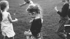O grupo de jardim de infância caçoa os amigos que jogam o divertimento do campo de jogos e a manutenção programada imagem de stock