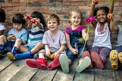 O grupo de jardim de infância caçoa os fazendeiros pequenos que aprendem a jardinagem fotografia de stock