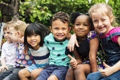 O grupo de jardim de infância caçoa amigos arma-se em torno do divertimento de assento e de sorriso foto de stock