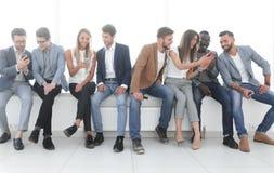 O grupo de jovens comunica-se na sala de espera imagem de stock
