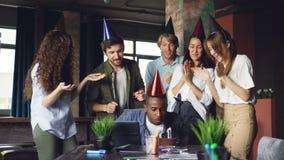 O grupo de jovens está felicitando o homem afro-americano no aniversário no escritório que traz o bolo e que aplaude as mãos, ind video estoque