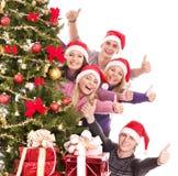 O grupo de jovens no chapéu de Santa mostra o polegar. Imagens de Stock
