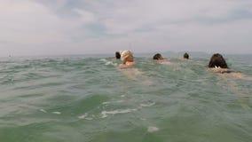 O grupo de jovens que nadam na câmera pov da ação do mar dos amigos aprecia a água junto na praia video estoque
