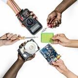 O grupo de mãos que guardam a eletrônica do computador parte no branco foto de stock royalty free